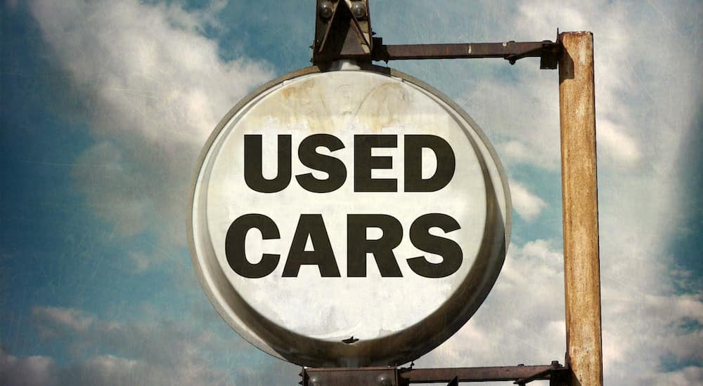 """Black and white """"USED CARS"""" sign on a rusted, brown pole against a blue sky with some clouds"""