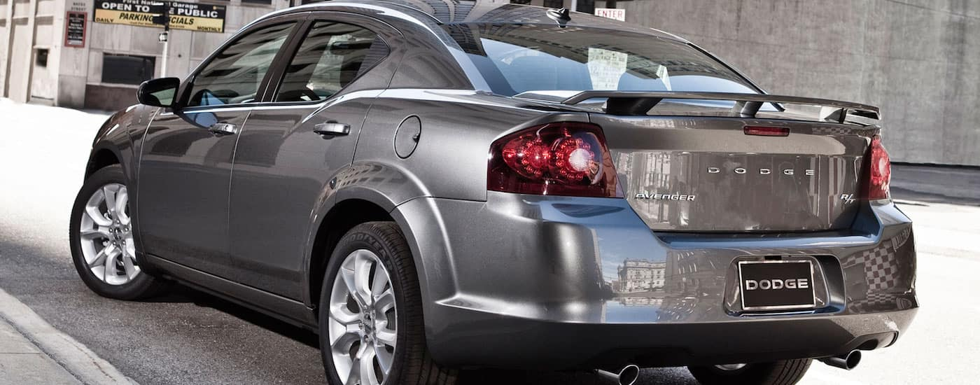 Closeup of the rear end of a Silver 2014 Used Dodge Avenger in a city