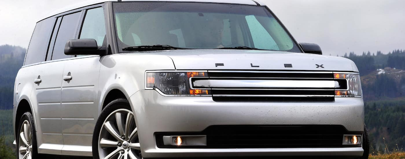 Closeup of the grille on a White 2012 Used Ford Flex with trees in the back