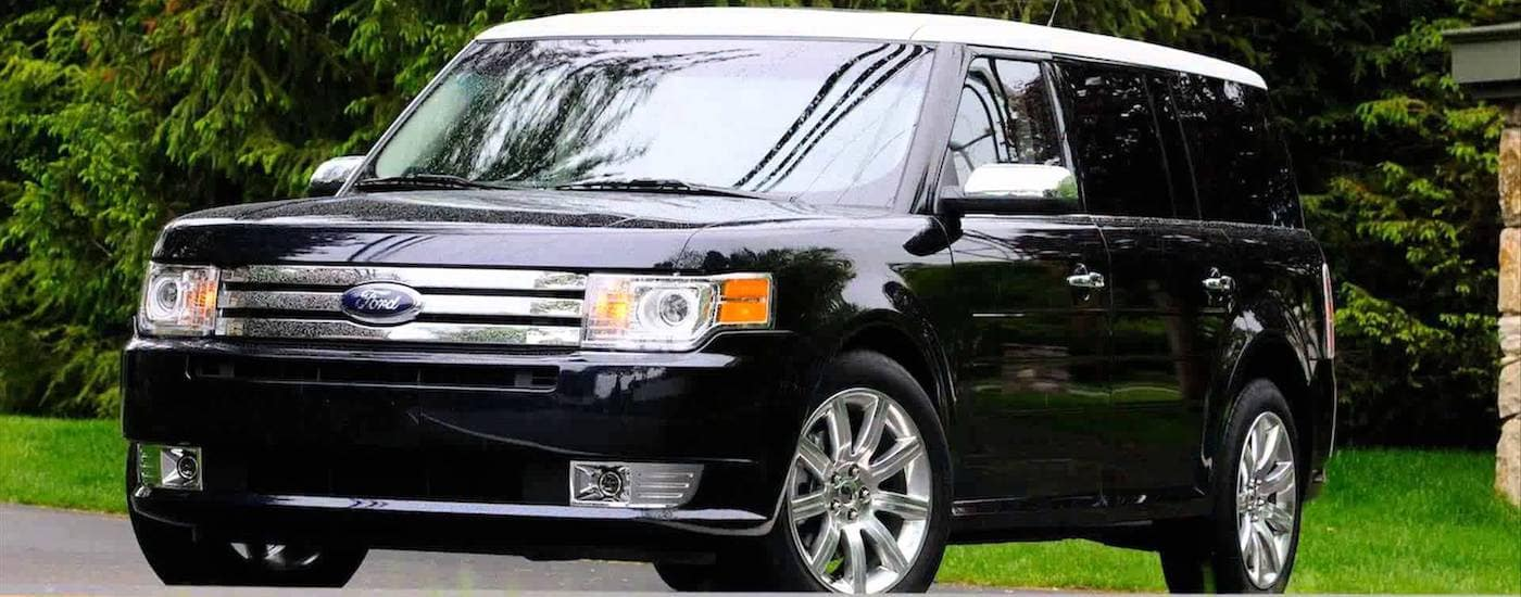 Black 2015 Used Ford Flex in front of evergreen trees