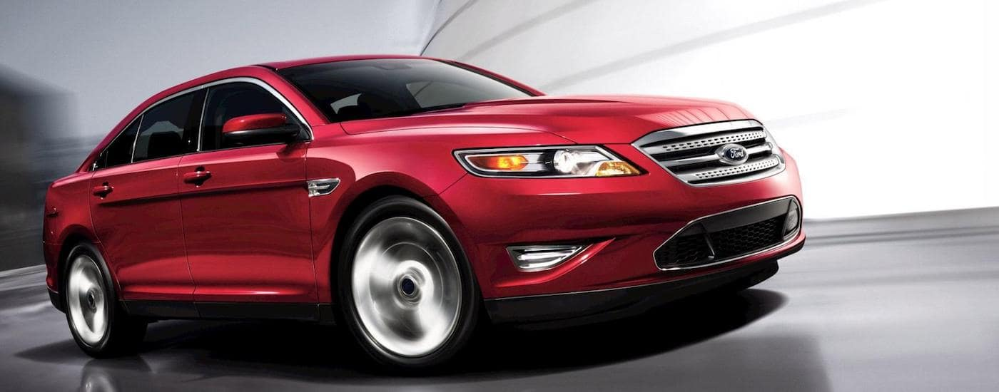 Red 2011 Used Ford Taurus racing around building