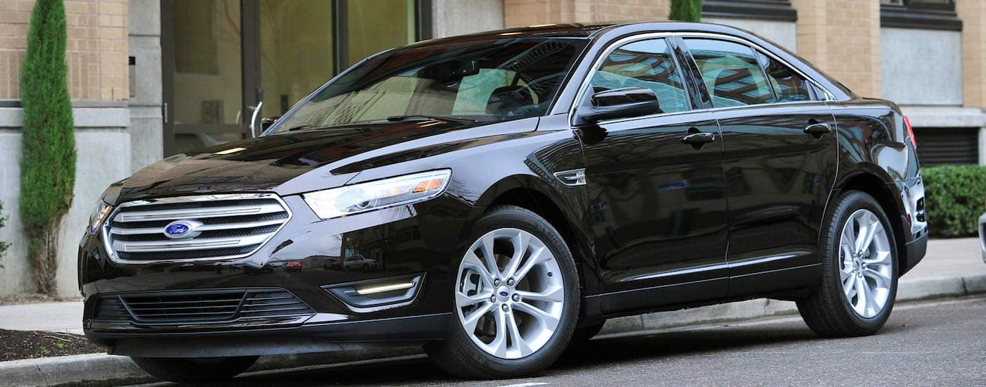 Black 2013 Used Ford Taurus parked in front of light brown building