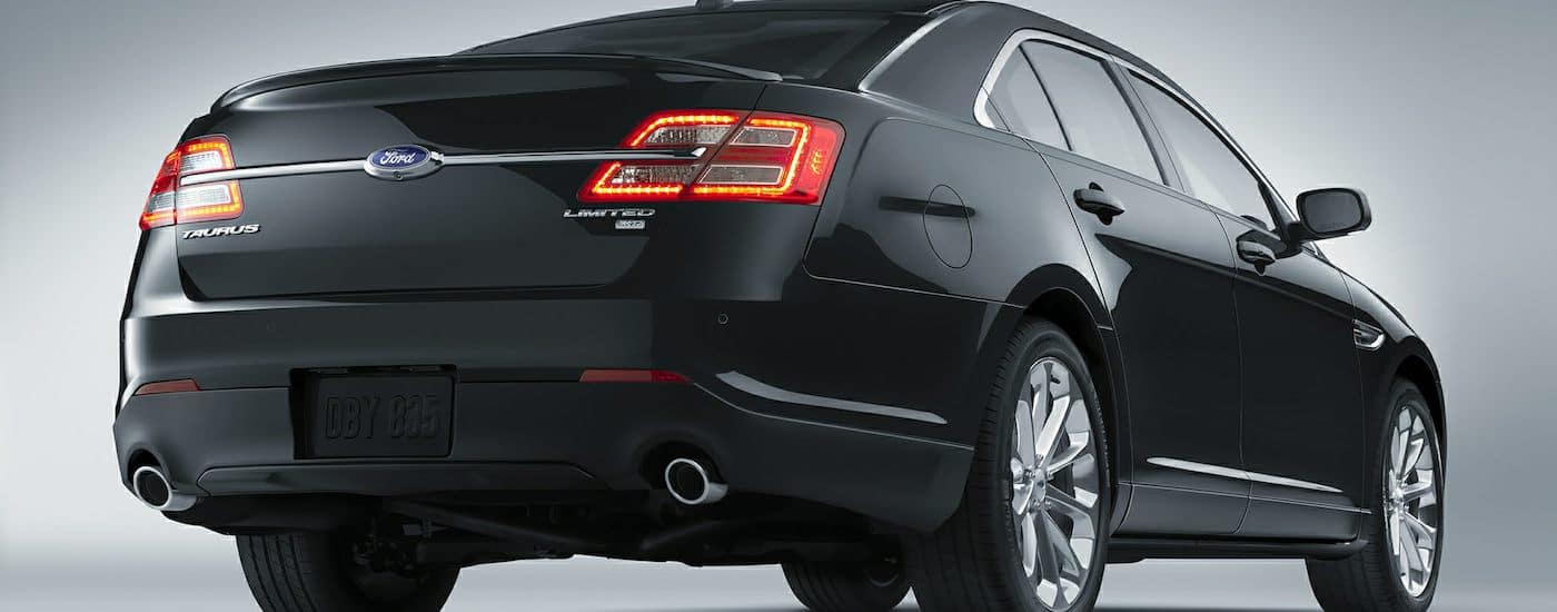 The back of a Black 2015 Used Ford Taurus on gray