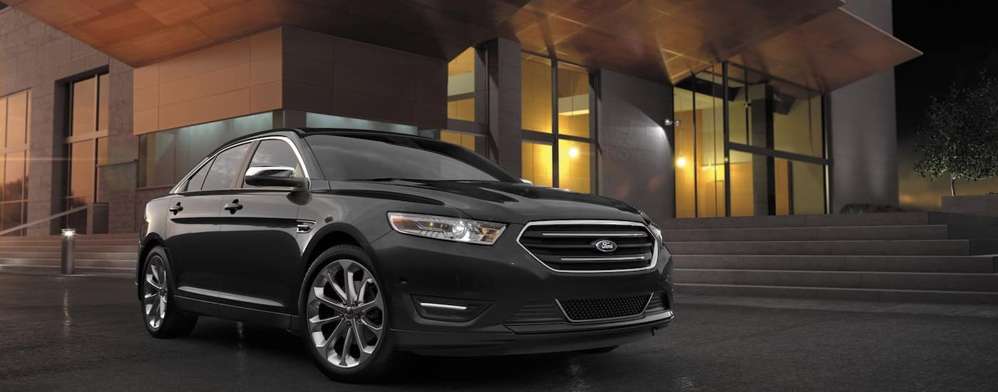 Black 2017 Used Ford Taurus in front of modern building at night