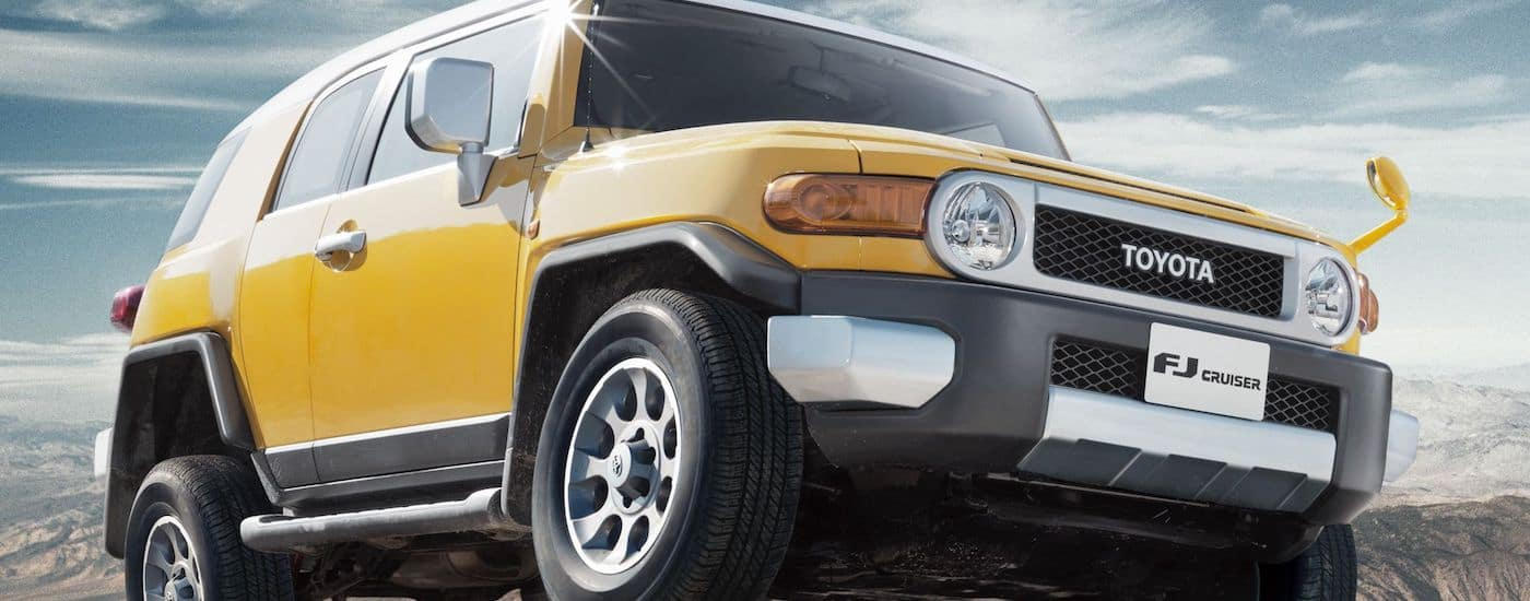 Yellow 2010 Used Toyota FJ Cruiser from a low angle climbing a mountain