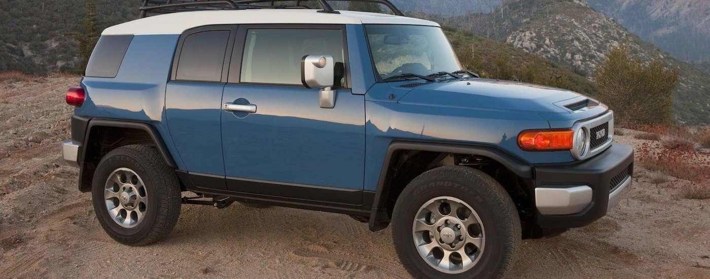 Blue 2012 Used Toyota FJ Cruiser on a hill with mountains in the back