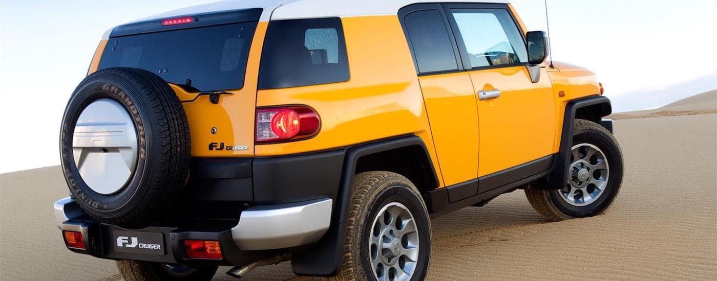 Yellow 2011 Used Toyota FJ Cruiser climbing a sand dune
