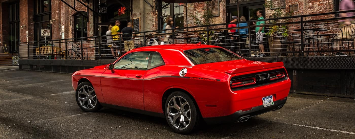 Red Used Dodge Challenger parked in the city street