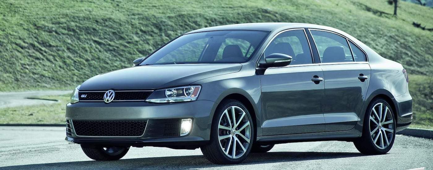 Silver 2012 Used Volkswagen Jetta in front of a grassy hill