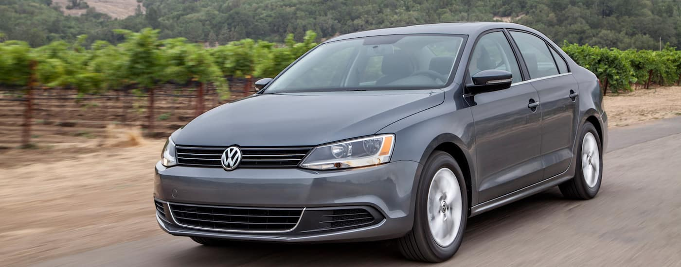 Silver 2014 Used Volkswagen Jetta driving by winery