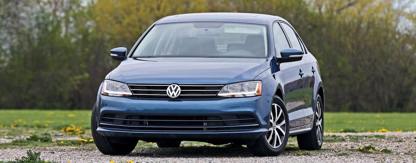 Blue 2017 Used Volkswagen Jetta with trees in distance