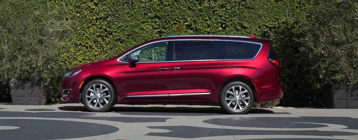 Red 2017 used Chrysler Pacifica parked in front of bushes