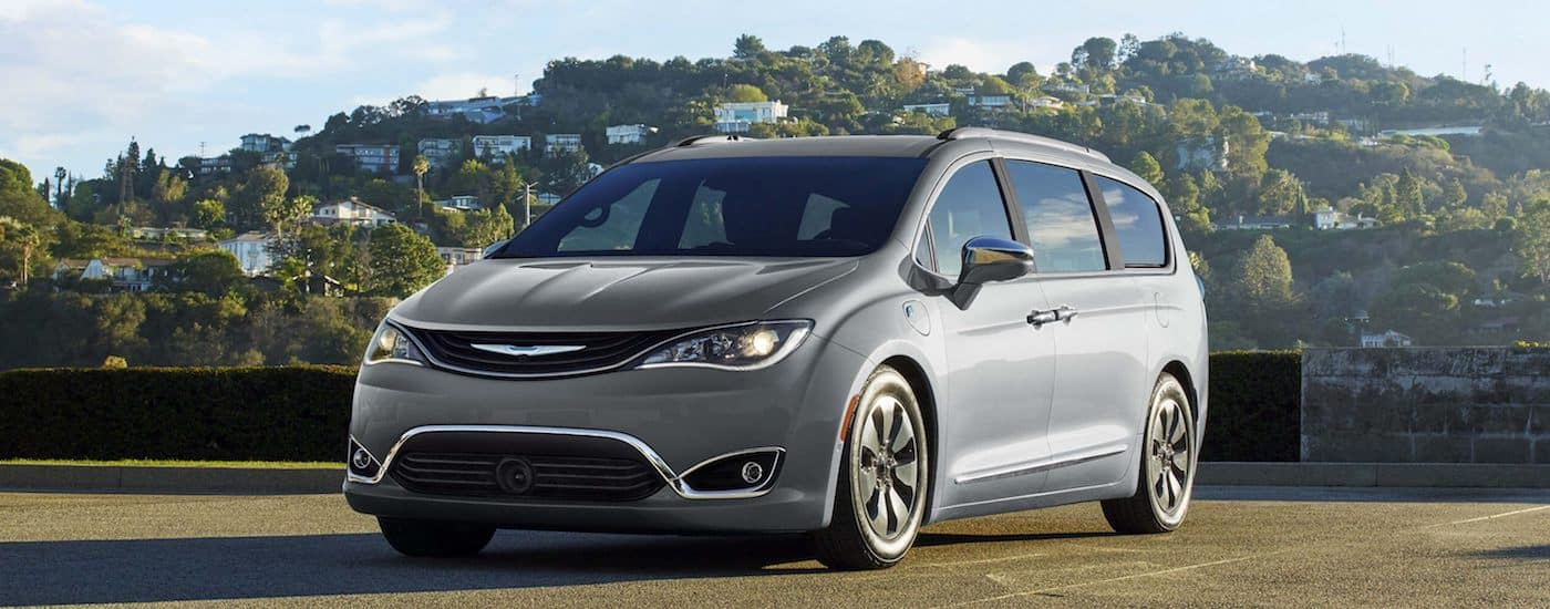 Silver 2018 Used Chrysler Pacifica in a parking lot in front of a hill with houses