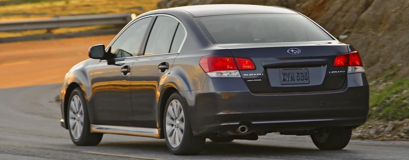 Grey 2010 Used Subaru Legacy driving on mountain road