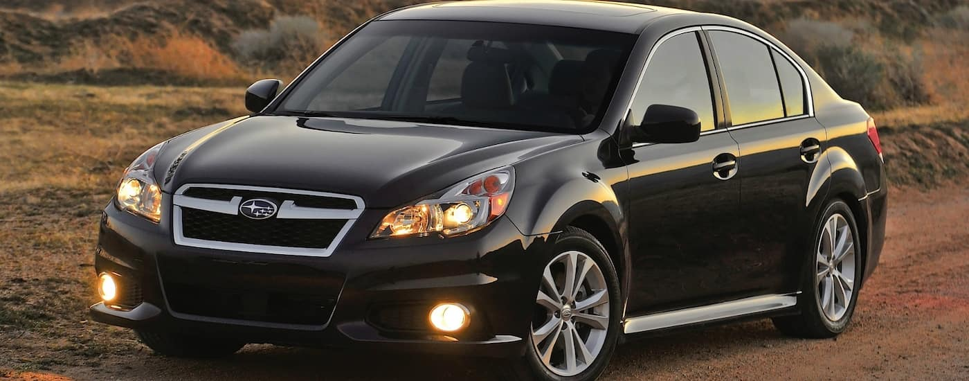 Black 2012 Used Subaru Legacy driving on dirt road at dusk