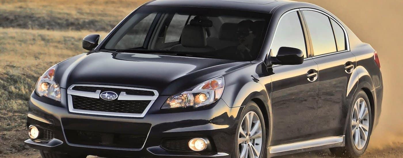 Black 2013 Used Subaru Legacy driving on dirt road