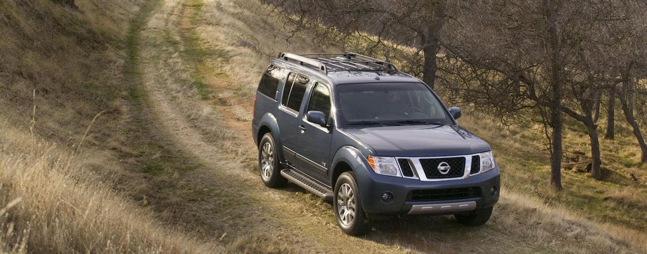 A blue used Nissan Pathfinder navigates a dirt trail through the trees