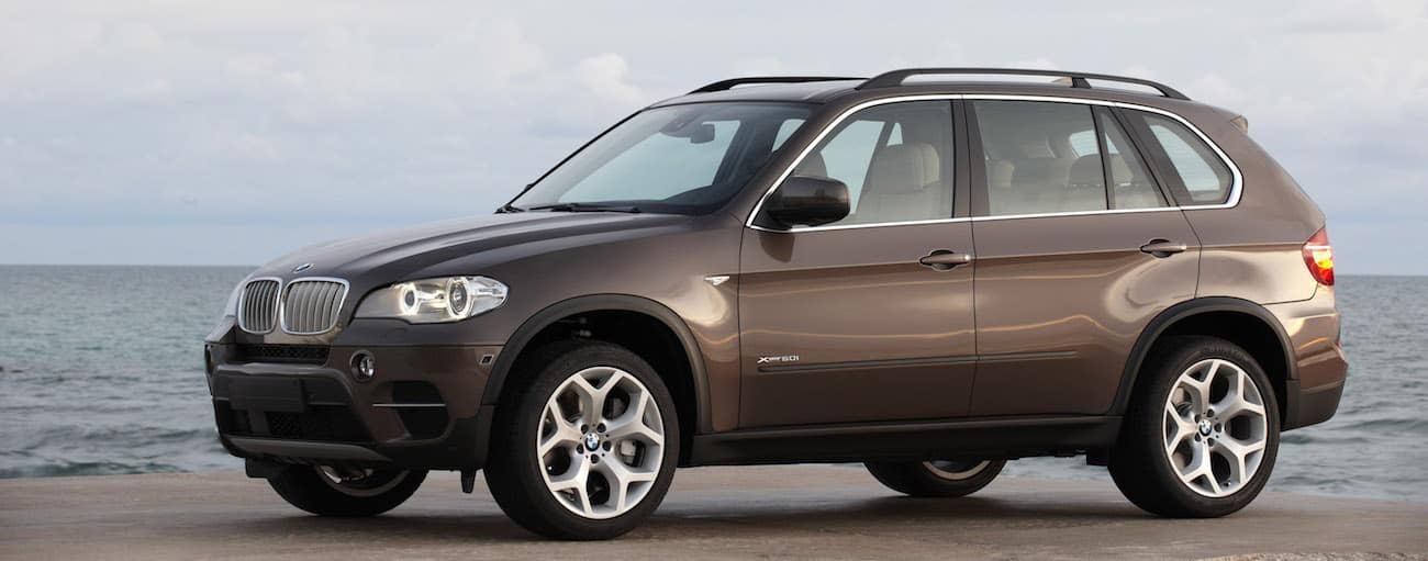 A dark silver used BMW X5 in front of the ocean