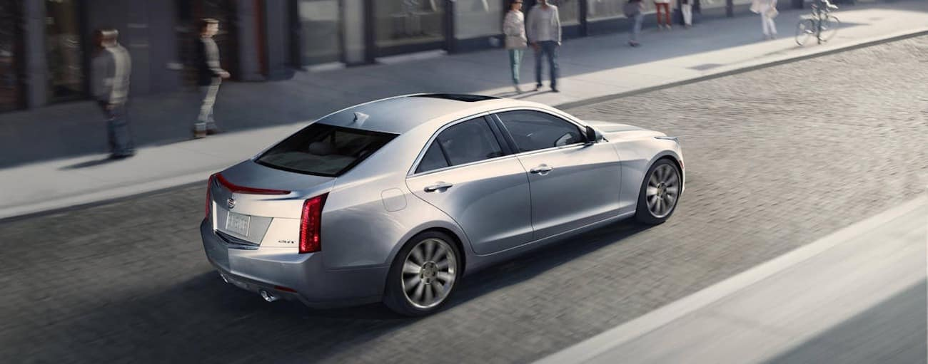 A silver 2014 used Cadillac ATS driving on a cobblestone road