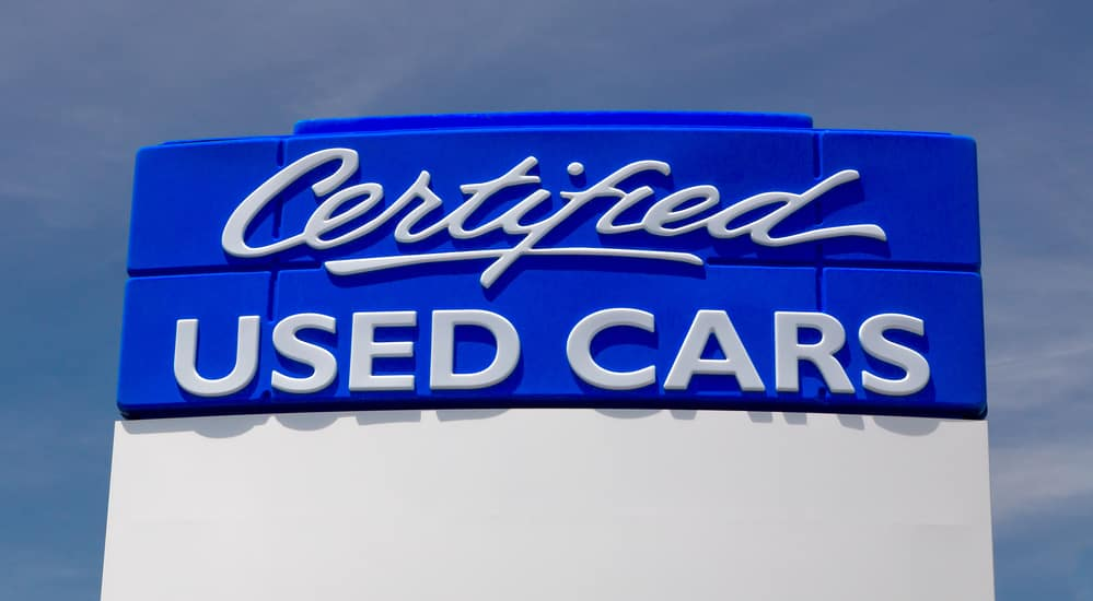Large blue certified used cars sign against cloudy blue sky