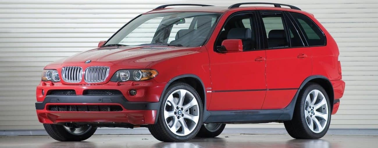 Bright red 2006 used BMW X5 in front of a garage door