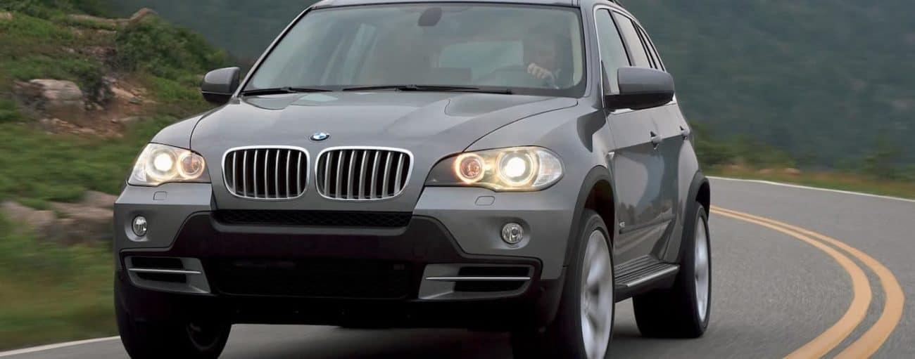 Silver used BMW X5 Drives down a twisty road