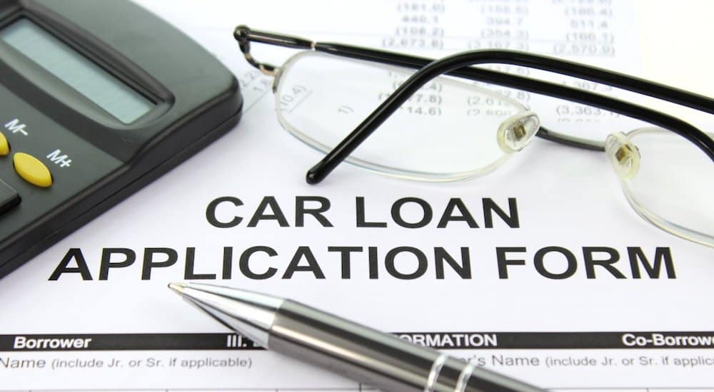 A paper car loan application with pen, glasses and calculator