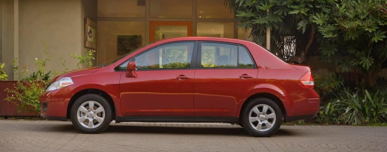 A red 2011 used Nissan Versa parked in front of a house