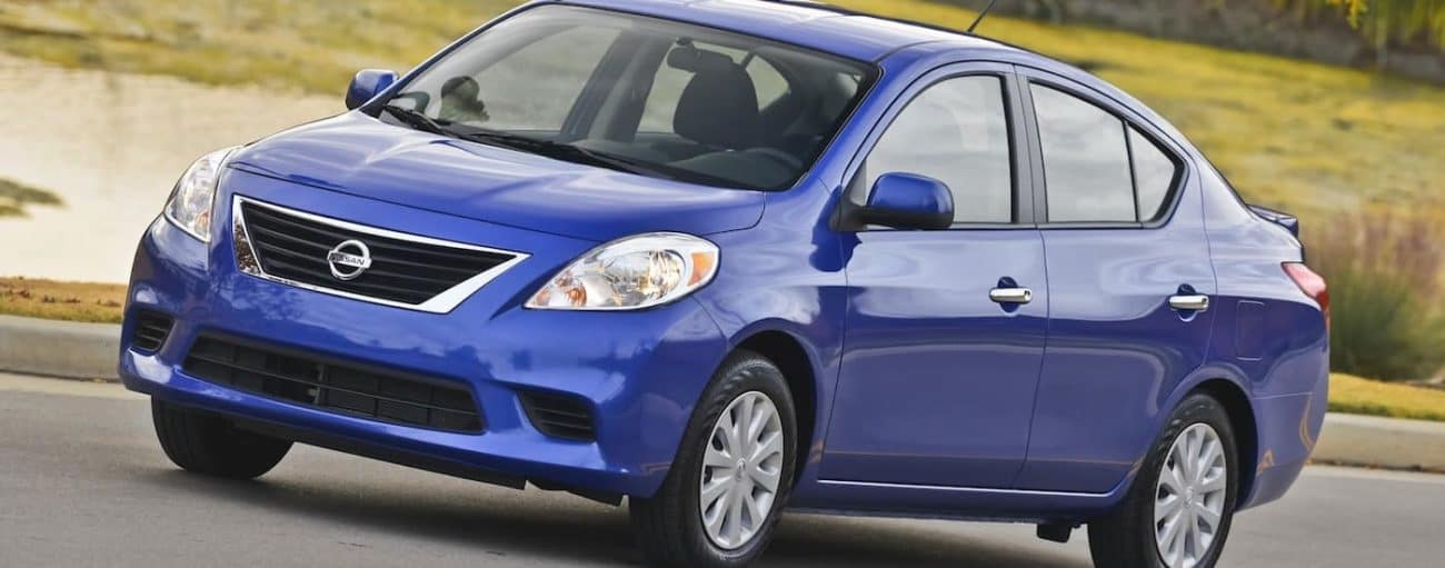 A dark blue used Nissan Versa driving by a park