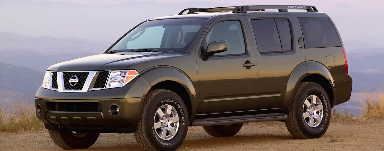 A dark grey 2006 used Nissan Pathfinder on a mountain at sunset
