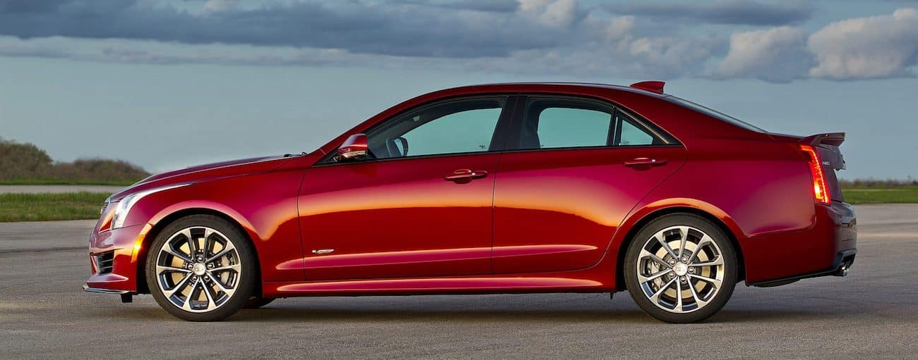 A red 2016 used Cadillac ATS on a track with a blue sky in the horizon