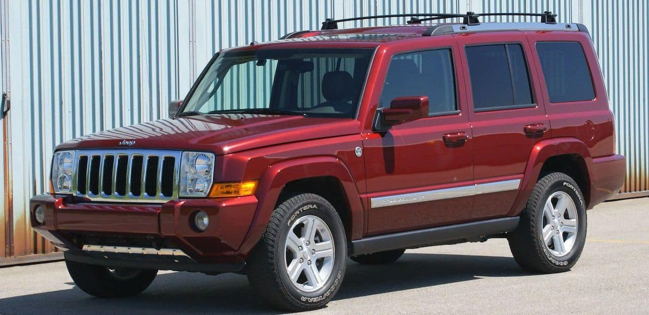Red 2006 used Jeep Commander in front of metal shipping container