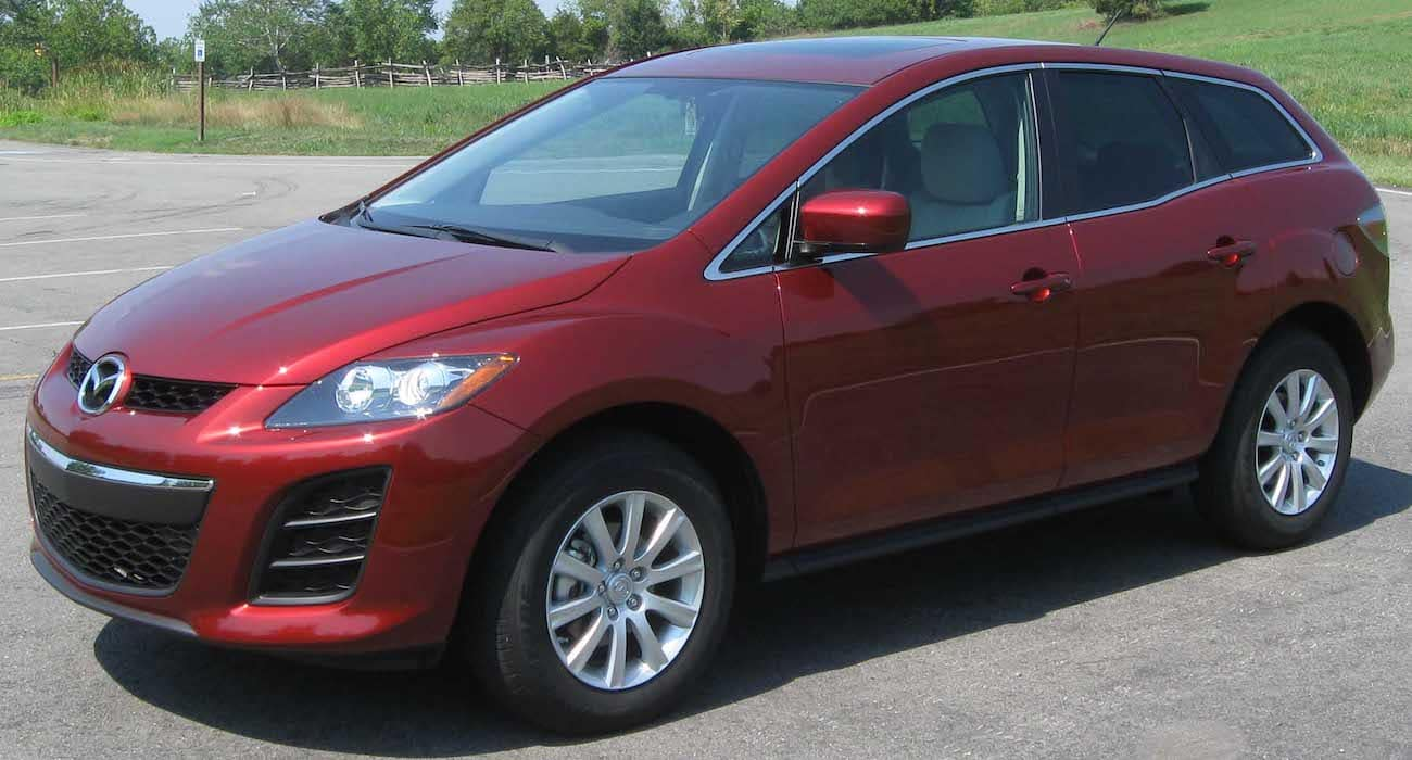 Red 2010 used Mazda CX-7 in front of field with wooden fence in distance
