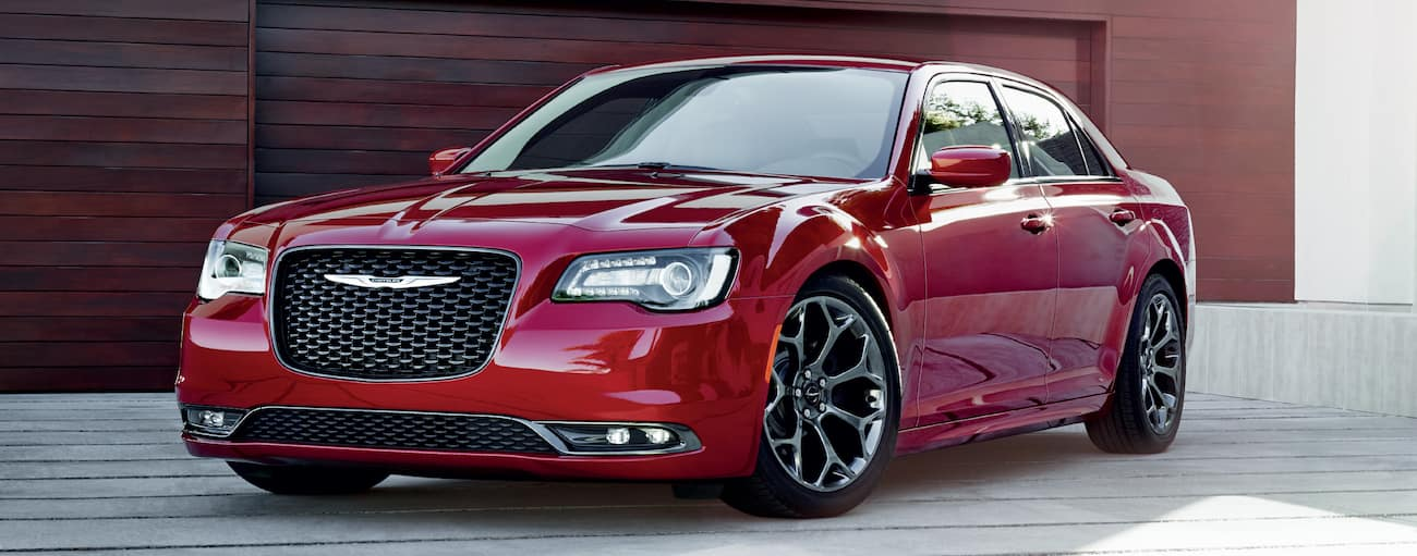 Red 2018 Chrysler 300 in front of wooden garage