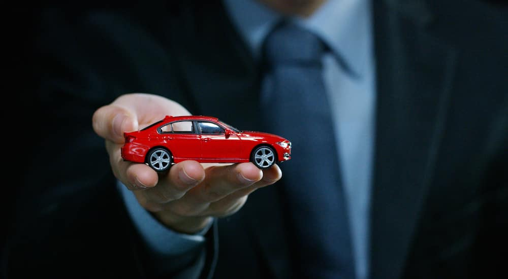 Man in suit holding a red toy car