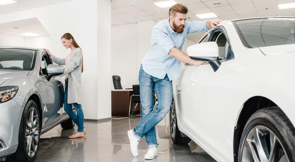 Man and woman looking at cars in showroom
