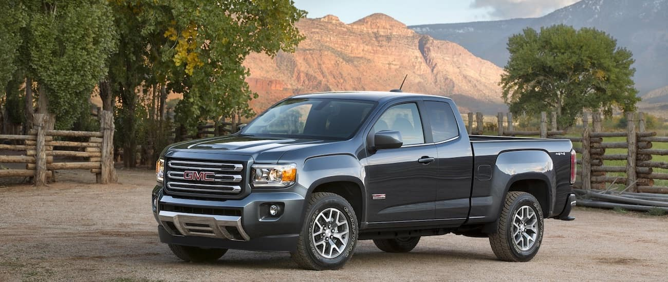 A dark blue 2015 used GMC Canyon in front of mountains