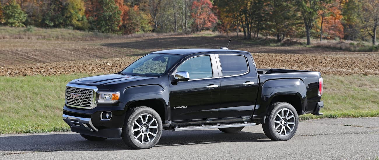 Black and chrome 2017 used GMC Canyon Denali in front of a field in fall