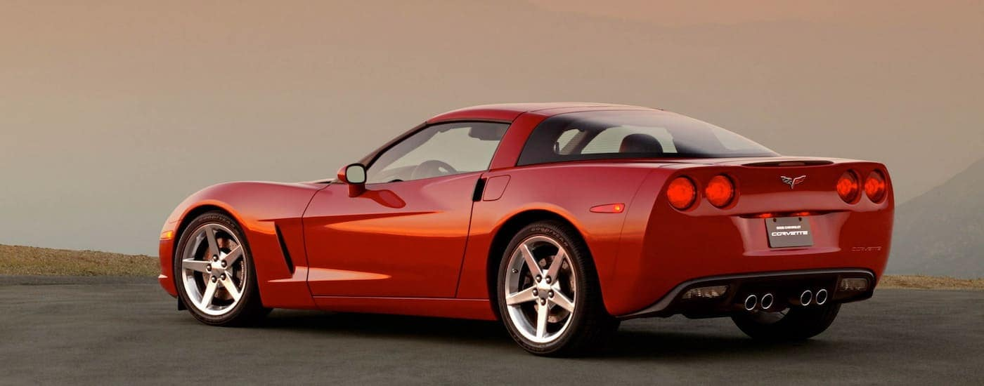 A deep red 2005 used Chevy Corvette is parked on a hazy mountain top.