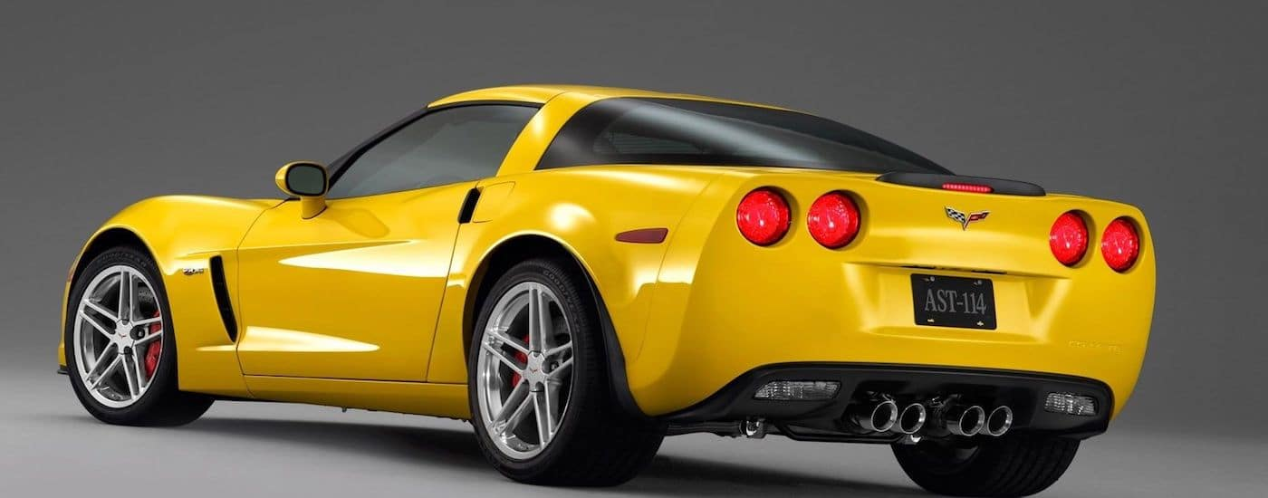 A yellow 2008 used Chevy Corvette is shown in a grey showroom from the rear.