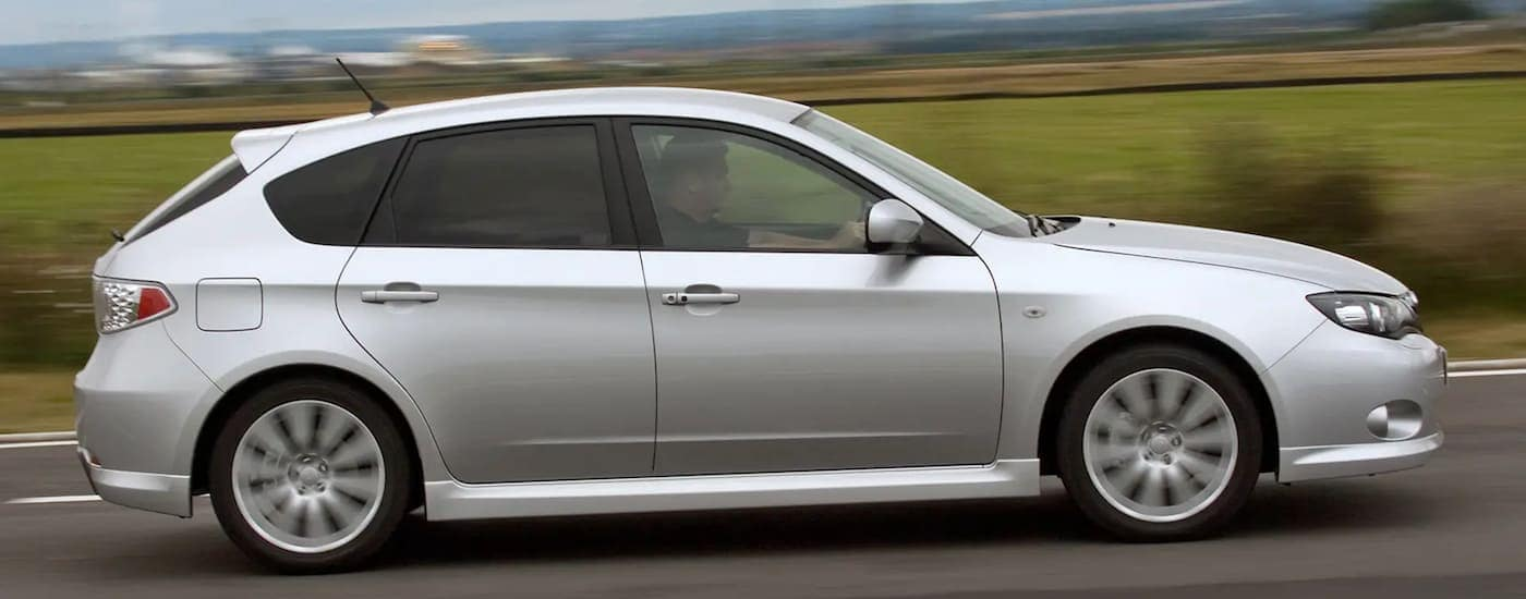 A clean silver 2008 used Subaru Impreza driving by a field