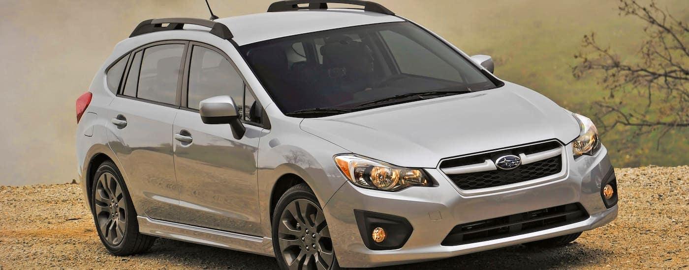 A silver 2012 used Subaru Impreza rockets downs a dusty dirt road