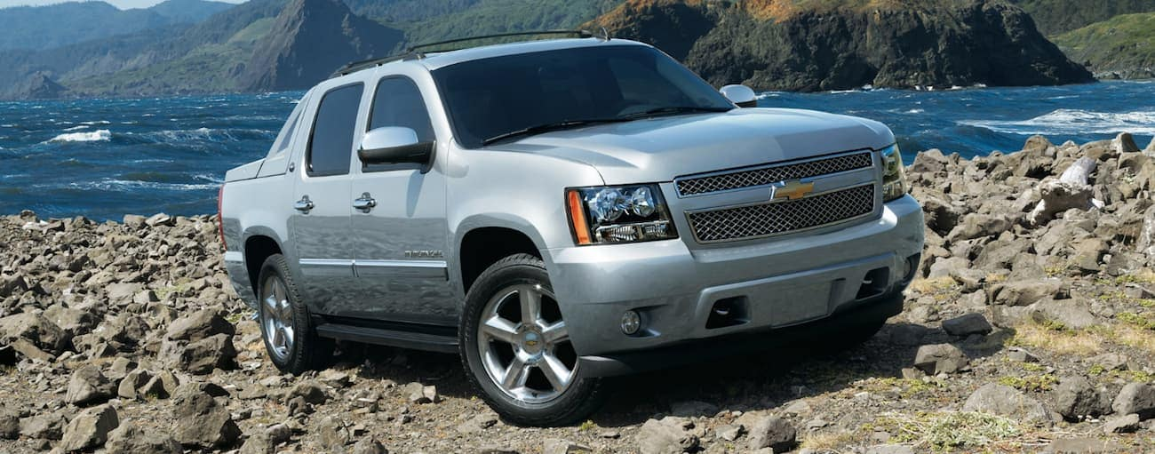 Silver 2013 used Chevy Avalanche climbing rocks at beach