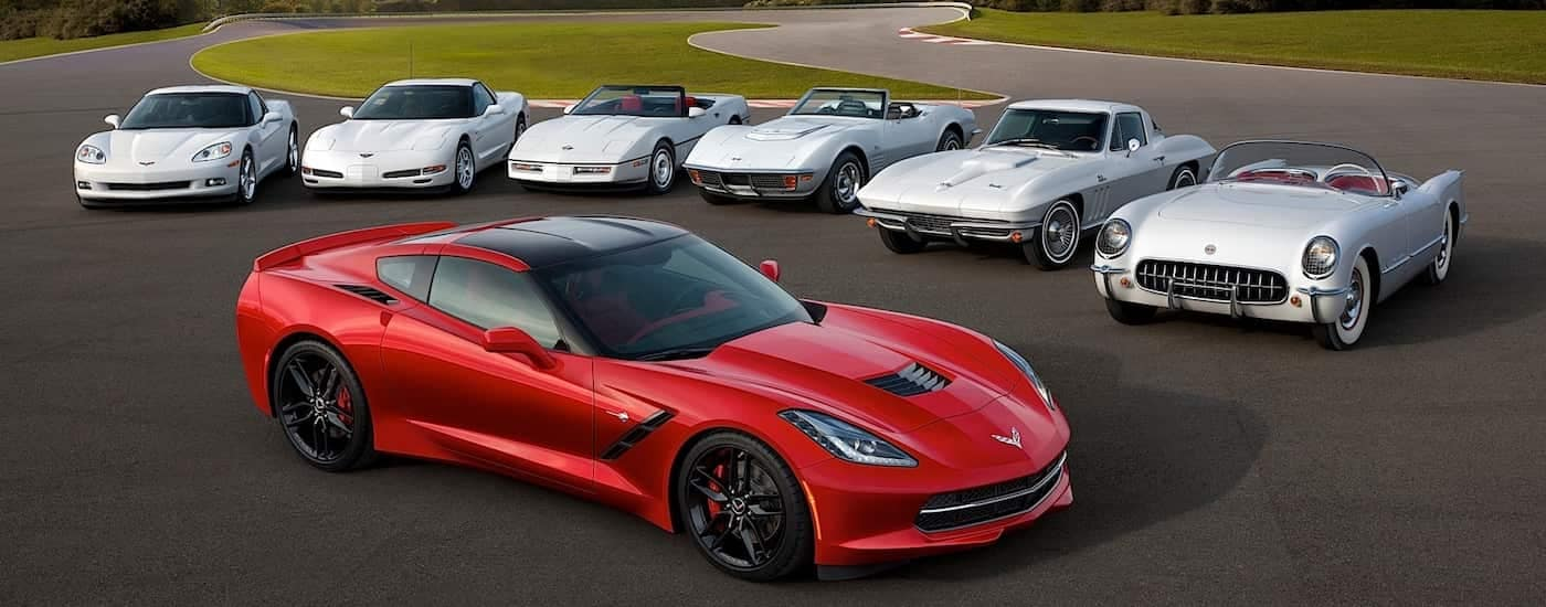 A red 2013 used Chevy Corvette is in front of 6 white classic Corvette generations.
