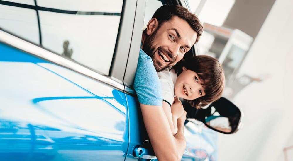 Man and child leaning out of blue car