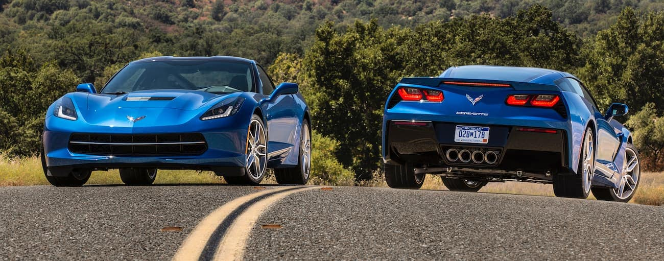 Two blue 2014 used Chevy Corvette C7s are side by side on a road. One facing forward, the other away