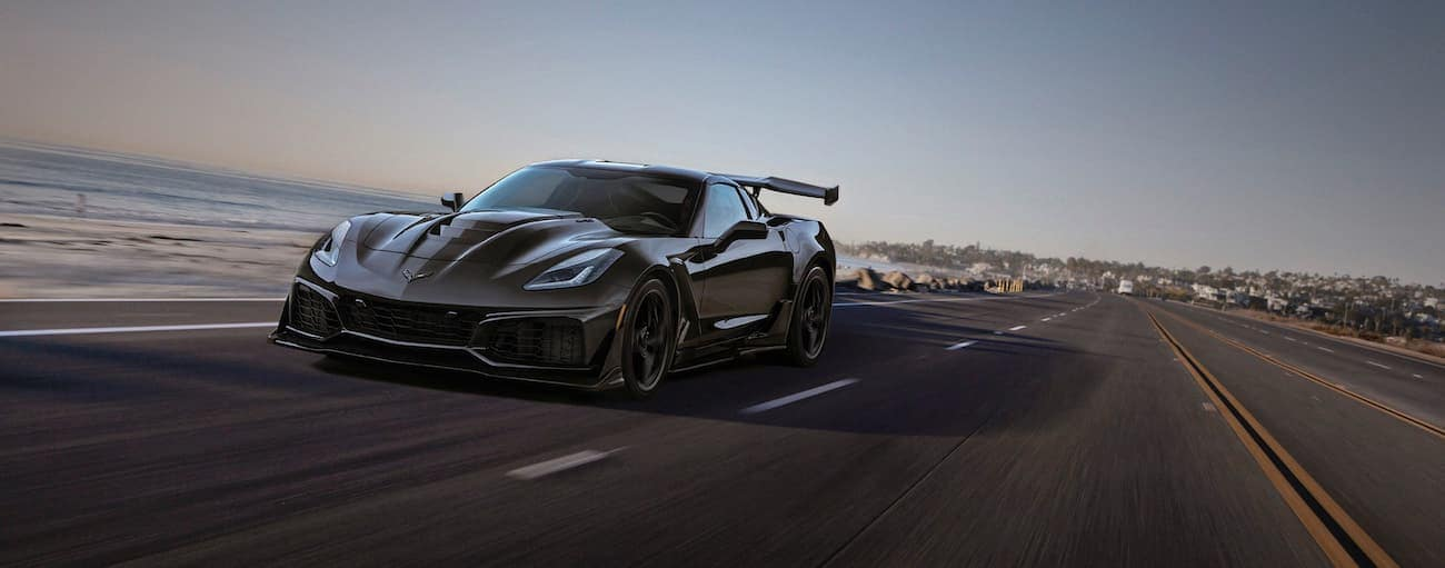 A black 2019 Chevy Corvette ZR1 is driving past the ocean.