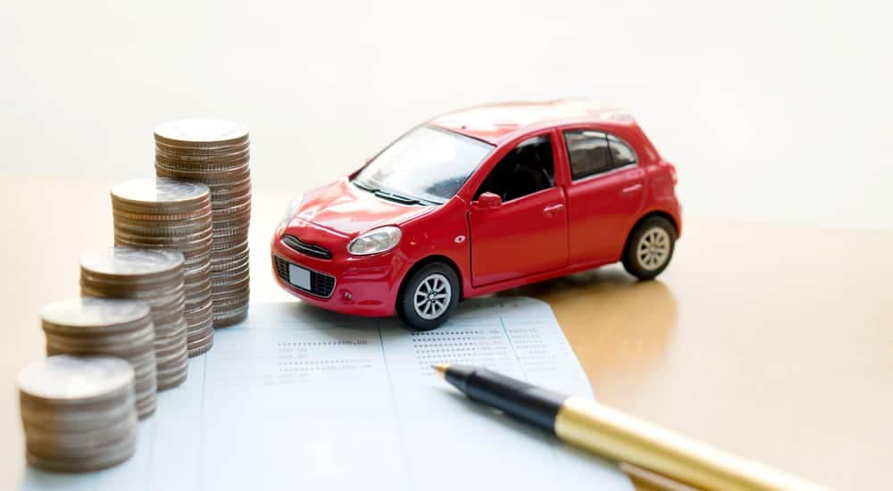 A red toy car next to stacks of coins a pen and paper