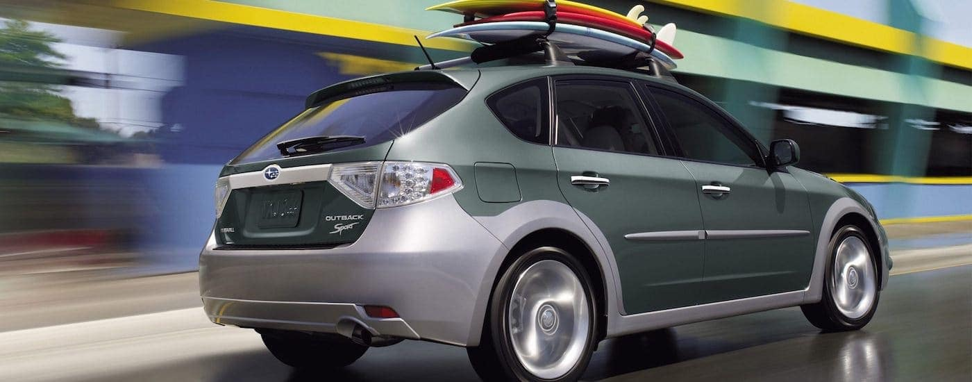 A teal and silver 2011 used Subaru Impreza Outback Sport with surfboards on the roof racing down a highway