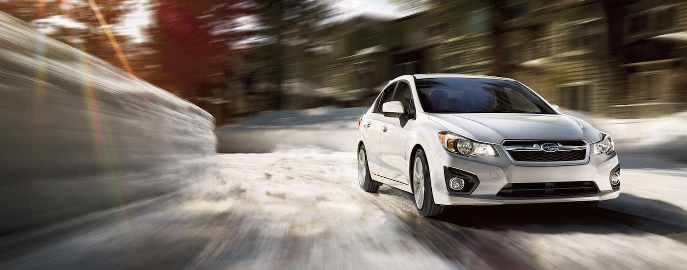 A white 2014 used Subaru Impreza navigates a snowy rural road